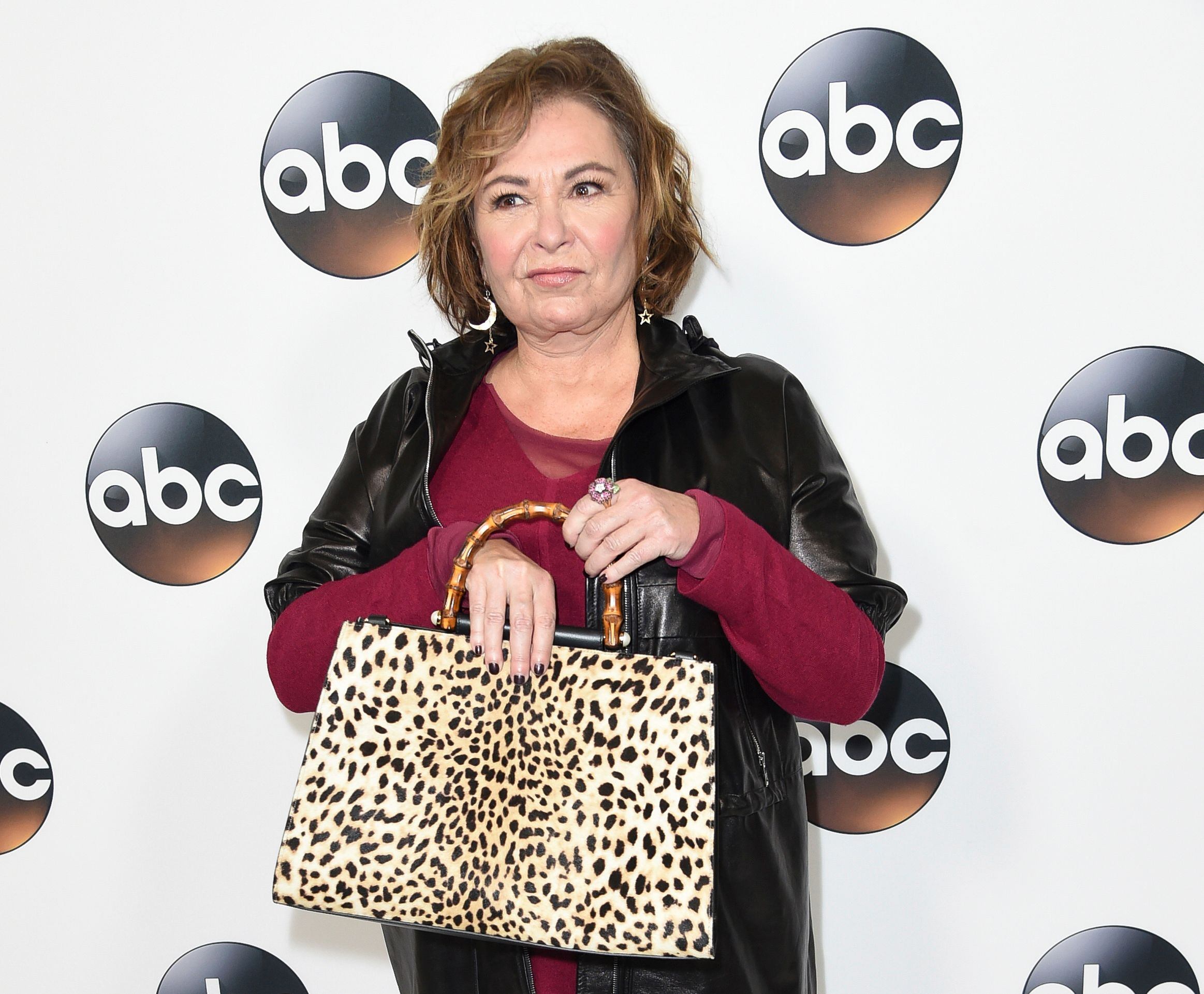 Roseanne posing in front of an ABC backdrop