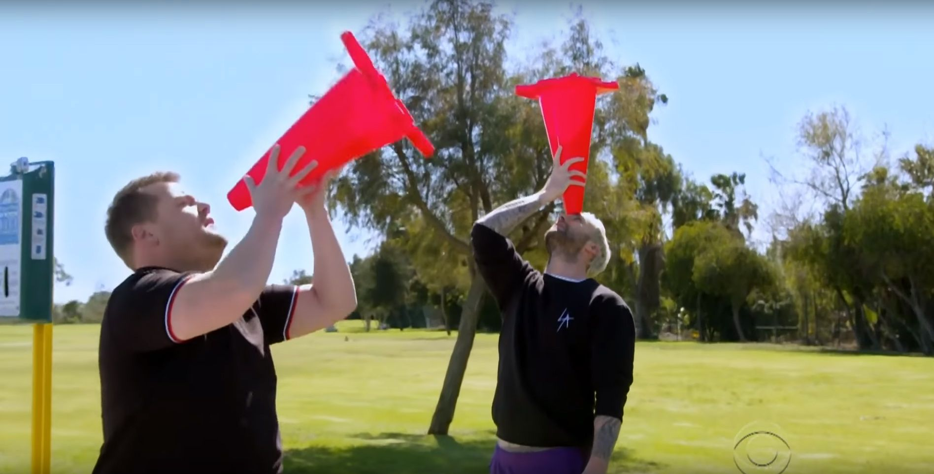 Adam Levine and James Corden balancing pylons on their faces